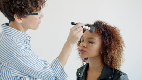 Slow motion of make-up artist applying cosmetics on beautiful young mixed race Live Action