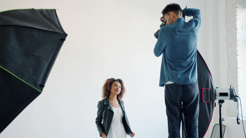 Mixed race model posing in studio while man photographer taking photos with Live Action