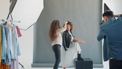 Slow motion of model working with stylist and photographer indoors in studio Live Action