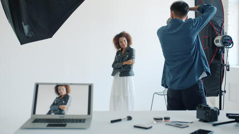 Backstage of photo studio: photographer taking pictures of pretty mixed race Live Action