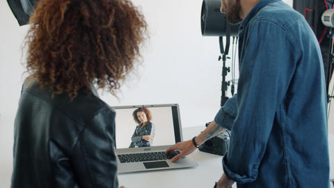 Photographer showing photos to mixed race model using laptop computer in studio Live Action