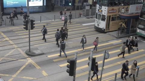 Pedestrians pass big wide cross road in Hong Kong city center Footage