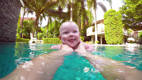 Happy Baby Boy Playing with Mommy in the Pool. UltraHD video Footage