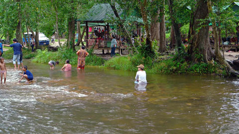 Families bathing in the refreshing water of the river at Phnom Kulen Footage