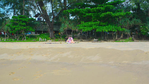 Gentle waves caress a pristine. white sand beach on the island of Phuket Live Action
