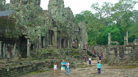 Tourists strolling through the ancient courtyard of Bayon Temple. Video UltraHD Live Action