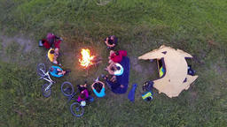 Aerial: Group of campers sitting around the camp fire and talking Footage
