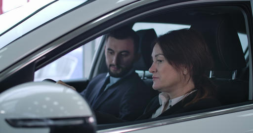 Adult Caucasian woman and young man sitting in car and talking. Female client Live Action