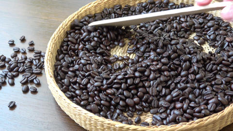 Roasted coffee beans closeup. Fragrant coffee beans. Scoop stir coffee beans Live Action