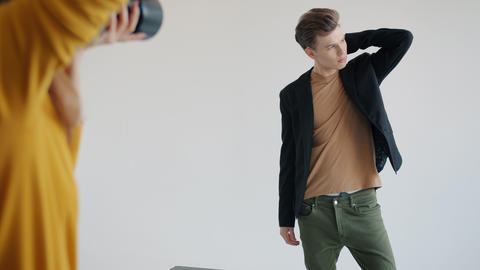 Good-looking male model posing wearing trendy clothes indoors in photo studio Live Action