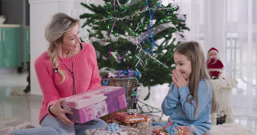 Young Caucasian attractive woman giving Christmas present to cute girl. Mother Live Action