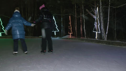 Back view of mother with child skating on ice at night time Live Action