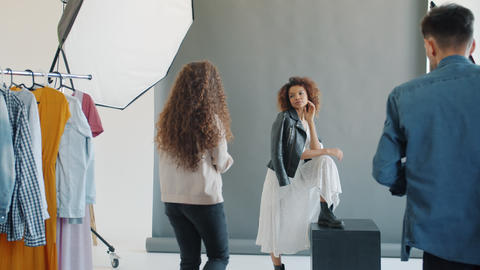 Stylist putting on trendy hat on young model posing for camera in studio Live Action