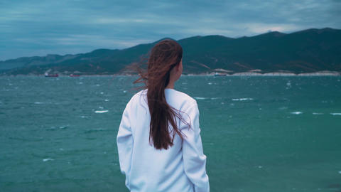 A girl stands with her back to the frame on the seashore in a storm. The girl on Live Action