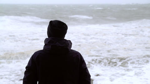 The man looks at the raging sea. A man is watching the storm. Silhouette of a Live Action