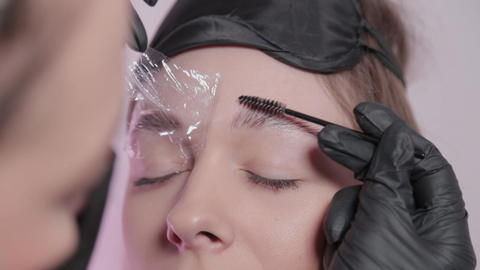 Woman master paints eyebrows to client Live Action