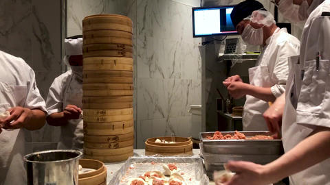 Chefs cooking Chinese dumplings by the traditional bamboo steamers in a Live Action