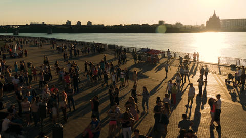 People walking and learning how to dance on city quay at sunset - slow motion Live Action