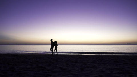 Young couple walking at beach at dusk Live Action