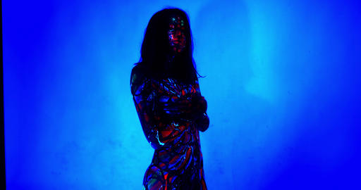 Young lady with glowing ultraviolet body art is posing on blue background, 4k Live Action