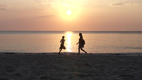Silhouette of young boy and woman running and walking Along the Beach at Sunset Live Action
