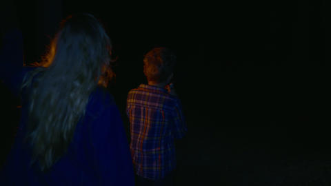 Teens girl and boy with oil lamp and flashlight walking in dark in summer forest Live Action