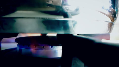 stove top burner igniting into a blue cooking flame in slow motion with pot on top, in a kitchen Live Action
