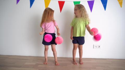 Creative little girls pretending cheerleaders holding pink pompon paper balls Live Action