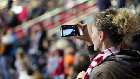 Close-up attractive girl makes video on the hockey stadium Footage