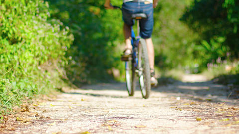 Man on Mountain Bike Rides on a Broad. Dirt Road. Video 3840x2160 Footage