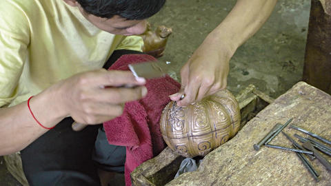 Local metalwork artisan carving intricate patterns into metal using hand tools Live Action