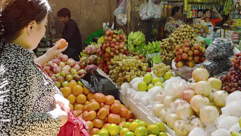 Local vendor sells fresh fruits and vegetables at crowded public market Footage