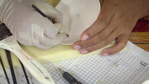 Artist carving intricate designs into ceramic plate with traditional hand tool Footage