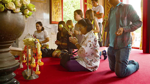 Buddhist worshippers kneel and give offerings before altar at Wat Chalong Footage