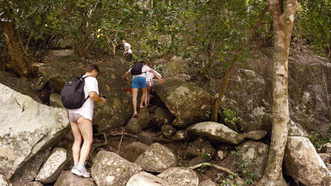 Tourists hike along a rugged and rocky nature trail at Ba Ho Waterfall Footage