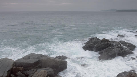 Waves and foamy waters wash over boulders on a rocky. tropical beach Footage
