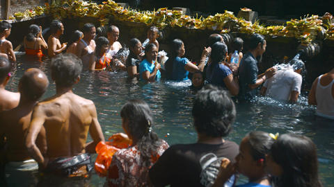 Unidentified worshipers bathing at Tirta Empul temple in Bali. Indonesia Footage