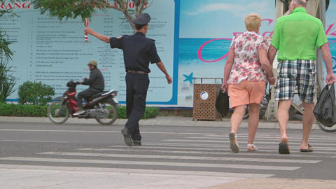 Traffic officer assists tourists in crossing a busy street in Nha Trang Footage