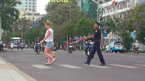 Tourist crossing a busy street in Nha Trang. with help from a traffic officer Footage