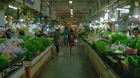 Customers buying fresh vegetables at an indoor public market in Phuket Footage