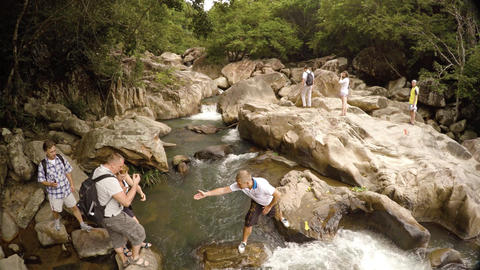 Tourists step precariously over rocks at Ba Ho Waterfall in Vietnam Footage