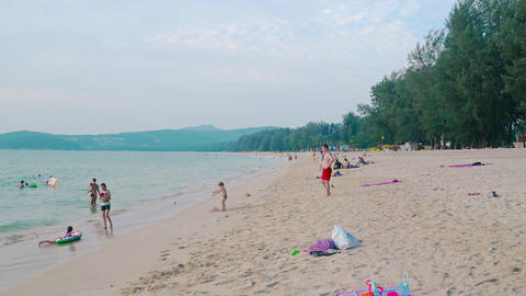 Happy tourists playing at this tropical beach paradise in Phuket. Thailand Footage
