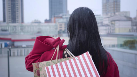 Back view of stylish lady with black hair standing with shopping bags, turning Live Action