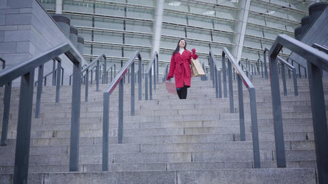 Long shot of young smiling Caucasian lady in red coat and black boots walking Live Action
