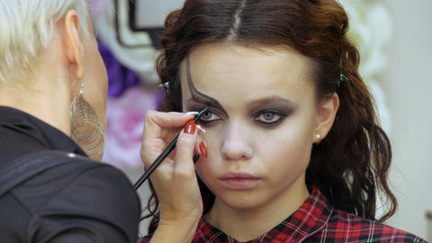 Easy Halloween Makeup. Girl in a beauty salon. Applying a stylistic pattern on Live Action