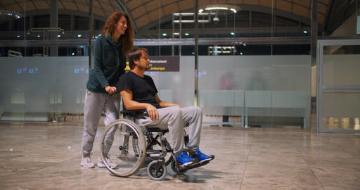 Happy disabled man in a wheelchair with happy young woman running at the airport Live Action