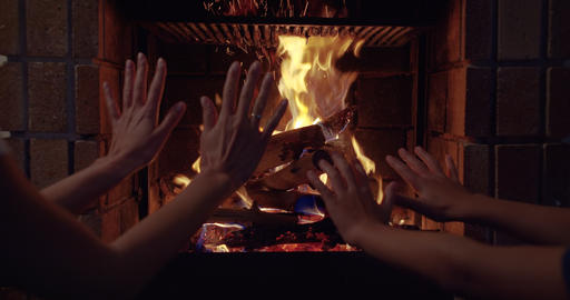 Couple hands warms his hands by the fire burning fireplace. Closeup of hands Live Action