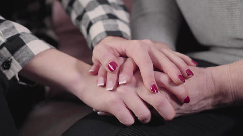Close-up of female Caucasian mature hands holding young teen hands. Unity of Live Action