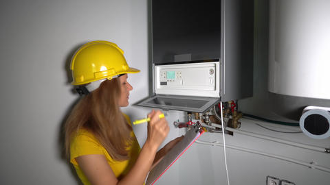 Engineer woman with helmet checking technical data of heating system equipment Live Action