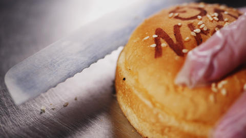 worker cuts hamburger bun with sesame seeds on metal table Live Action